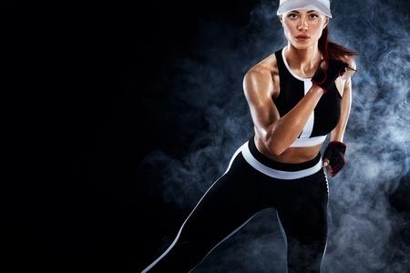 Forte velocista atletico donna, in esecuzione su sfondo nero che indossa l'abbigliamento sportivo. Fitness e motivazione sportiva. Concetto di corridore con copia spazio. Archivio Fotografico