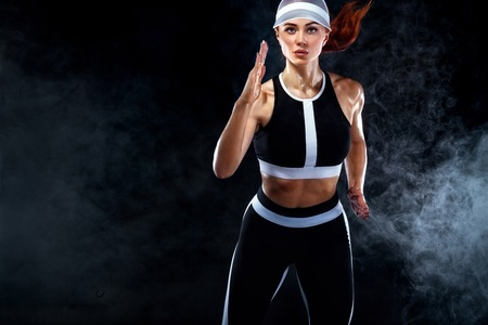 Strong athletic woman sprinter, running on black background wearing in the sportswear. Fitness and sport motivation. Runner concept with copy space.