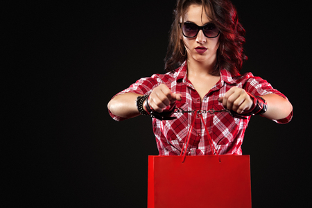 Black friday sale concept. Woman holding bags isolated on dark background. Handcuffed girl strapped to her bag. Hostage of shopping and sales.