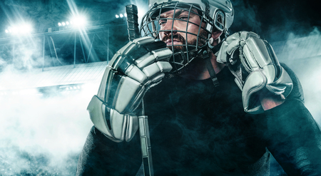 Ice Hockey player in the helmet and gloves on stadium with stick.