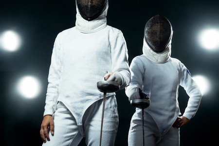 Young fencer athlete wearing mask and white fencing costume. holding the sword on black background with lights. Banque d'images
