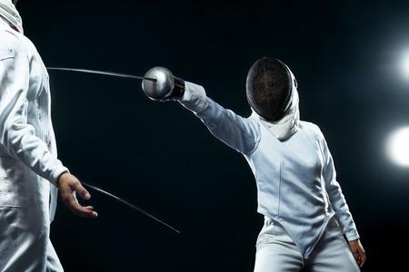 Jeune athlète escrimeur portant un masque et un costume d'escrime blanc. tenant l'épée sur fond noir avec des lumières.