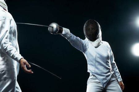 Young fencer athlete wearing mask and white fencing costume. holding the sword on black background with lights. Standard-Bild