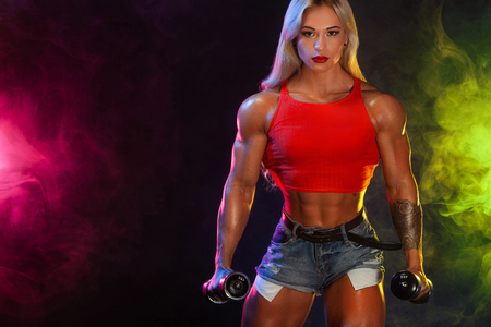Strong athletic russian woman bodybuilder with dumbbells on dark background wearing in sportswear. Fitness and sport motivation. Imagens