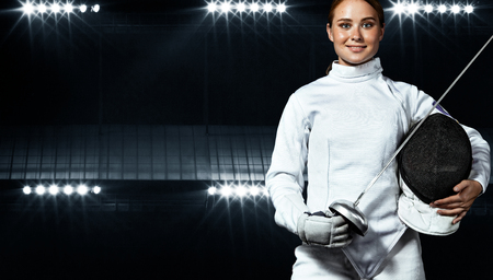 Young fencer athlete wearing fencing costume holding the sword and mask. Black background with lights.