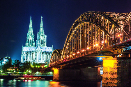 Cologne Cathedral and Hohenzollern Bridge at sunset, nighttime. Photo for postcard