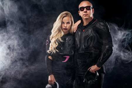 Fashion couple model DJ and biker with headphones and sunglasses, black leather jacket, leather pants, stylish pretty blonde woman and man in night casual outfit. Long wavy hairstyle. Stock fotó