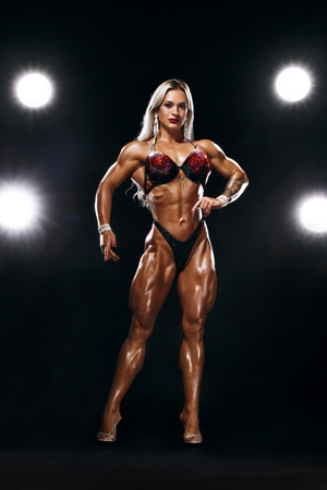 Bodybuilding competitions on the scene. Woman sportsmen and athlete. Black background with lights. Womens physique or bikini show on arena,