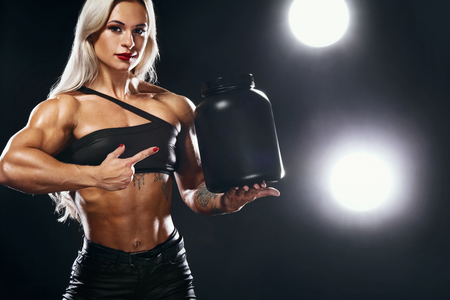 Athletic young woman bodybuilder on steroids have a cheat meal. Fitness and sport concept. Nutrition and bodybuilding. Stock Photo
