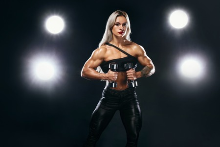 Strong athletic woman bodybuilder on steroids with dumbbells on dark background wearing in sportswear. Fitness and sport motivation. Standard-Bild