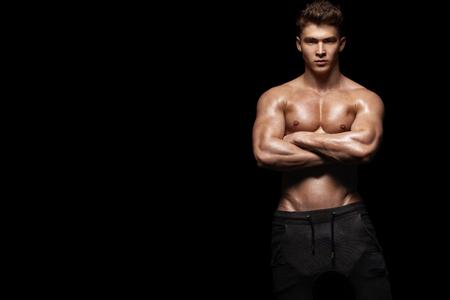 Close-up portrait of a brutal and fit man bodybuilder. Athlete bodybuilder on black background.