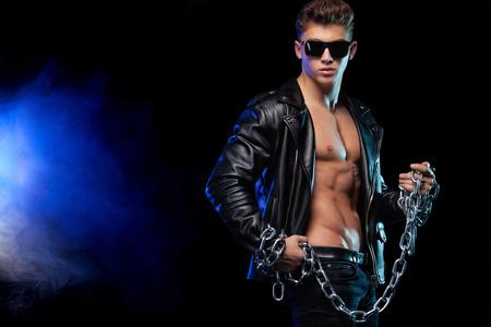 Herrenmode. Nahaufnahmeporträt eines brutalen und fitten Mannes in einer Lederjacke mit Ketten. Athletenbodybuilder auf schwarzem Hintergrund. Standard-Bild