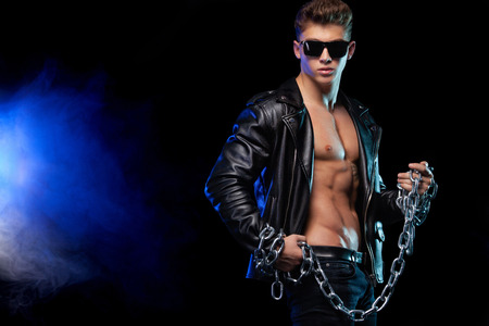 Men fashion. Close-up portrait of a brutal and fit man in a leather jacket with chains. Athlete bodybuilder on black background. Stock Photo