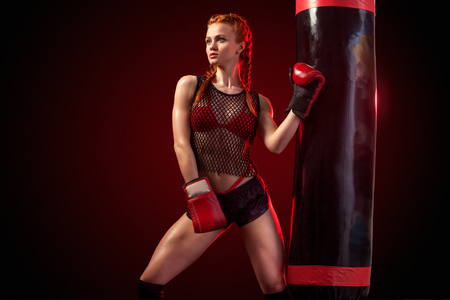 Young woman sportsman boxer doing boxing training at the gym. Girl wearing gloves, sportswear and hitting the punching bag. Isolated on black background with smoke. Copy Space. Stock Photo