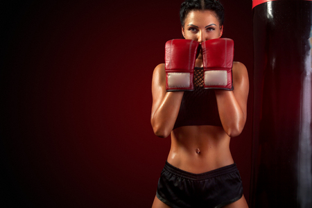 Young woman sportsman boxer doing boxing training at the gym. Girl wearing gloves, sportswear and hitting the punching bag. Isolated on black background with smoke. Copy Space. Imagens