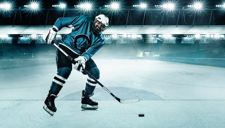 Ice Hockey player athlete in the helmet and gloves on stadium with stick. Action shot. Sport concept.
