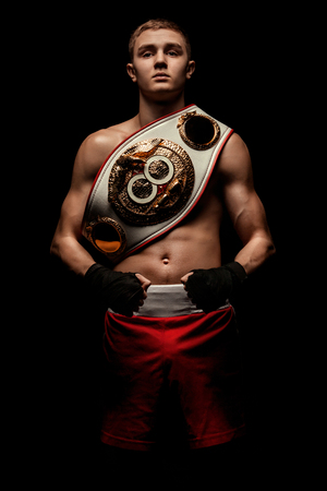 Sportsman, man boxer fighting in gloves with a championship belt. Isolated on black background with smoke. Copy Space.