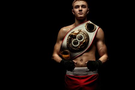 Sportivo, pugile uomo che combatte in guanti con una cintura da campionato. Isolato su sfondo nero con fumo. Copia spazio. Archivio Fotografico