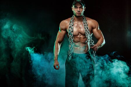 Muscular fitness sports man, atlete with chains in fitness gym. Фото со стока