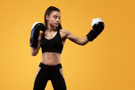 Sportsman, woman boxer fighting in gloves. on yellow background. Boxing and fitness concept. Stock Photo