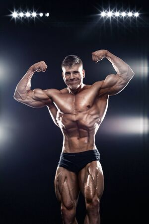 Strong muscular bodybuilder athlete man posing and pumping up muscles on black background. Workout bodybuilding concept. Фото со стока