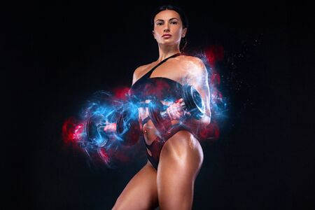 Strong muscular bodybuilder athletic woman pumping up muscles with dumbbells on black background. Workout bodybuilding and energy concept.