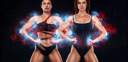 Two sporty and fit women athletes, bodybuilders. Workout and fitness motivation. Black background. Energy bodybuilding concept. 版權商用圖片