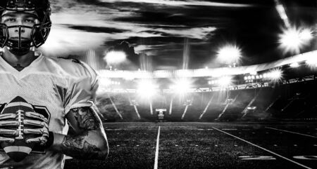 American football player, sportsman in helmet on stadium. Black and white photo. Sport wallpaper.