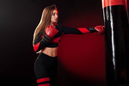 Young woman sportsman boxer doing boxing training at the gym. Girl wearing gloves, sportswear and hitting the punching bag. Isolated on black background with smoke. Copy Space. 스톡 콘텐츠