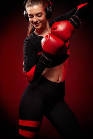 Happy and smiling young woman sportsman boxer on boxing training. Girl wearing gloves, sportswear.