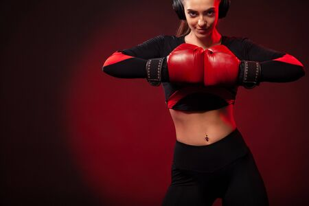 Young woman sportsman boxer on boxing training. Girl wearing gloves, sportswear.