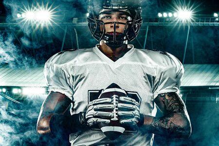 Giocatore di football americano, in casco sullo stadio. Concetto di azione sportiva. Archivio Fotografico