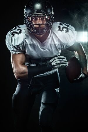 American football sportsman player in helmet on black background with smoke. Sport and motivation wallpaper.