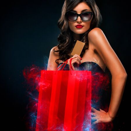 Black friday sale concept. Shopping woman holding red bag isolated on dark background in holiday Stock Photo
