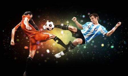 Soccer and sport concept. Two players in action to kick the ball at the football game on dark background with lights and bokeh