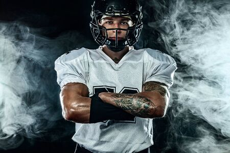 American football player, sportsman in helmet on black background with smoke. Sport and motivation wallpaper.