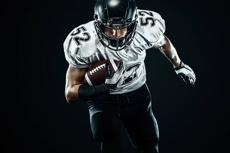 American football sportsman player in helmet isolated run in action on black background. Sport and motivation wallpaper. Standard-Bild