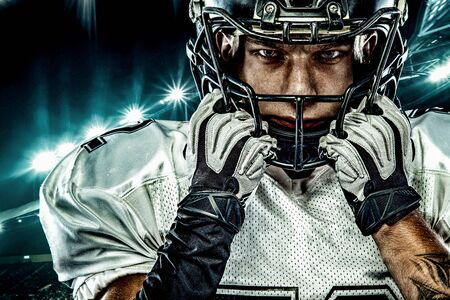 American football player. Sportsman with ball in helmet on stadium in action. Sport wallpaper. Closeup portrait. Stock Photo