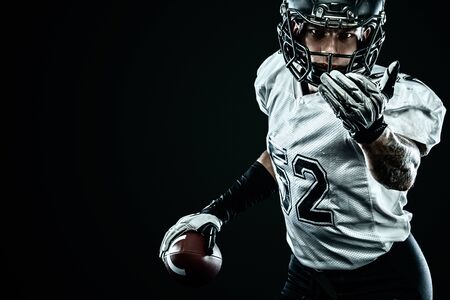 American football sportsman player in helmet isolated on black background. Sport and motivation wallpaper. Stock Photo