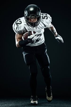 American football sportsman player in helmet isolated run in action on black background. Sport and motivation wallpaper. Stock Photo