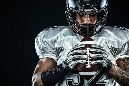 Giocatore di football americano sportivo in casco isolato eseguito in azione su sfondo nero. Carta da parati sportiva e motivazionale. Sport di squadra, Archivio Fotografico