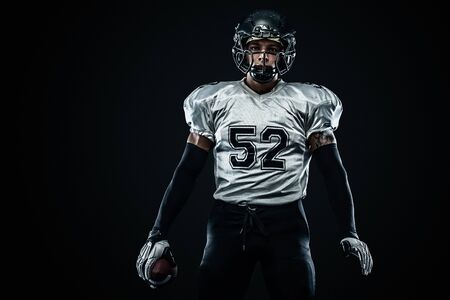 American football sportsman player in helmet on black background. Sport and motivation. Team sports. Standard-Bild