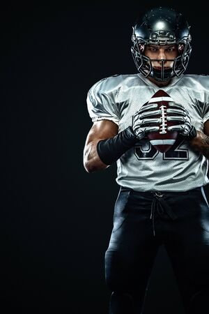 American football sportsman player in helmet on black background. Sport and motivation. Team sports. Stock Photo
