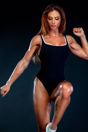 Beautiful fitness woman athlete and bodybuilder with perfect body wearing sport clothes for the gym training. Individual sports. Sports recreation. Stock Photo