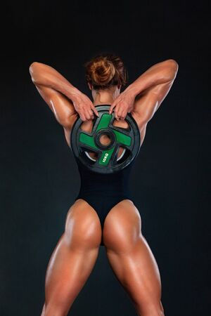Young fitness woman athlete and bodybuilder with barbell. Individual sports. Sports recreation. Sexy beautiful ass in thong.