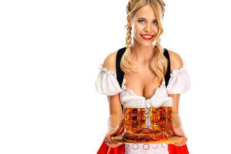 Junge Oktoberfest-Kellnerin, die ein traditionelles bayerisches oder deutsches Dirndl trägt und große Bierkrüge mit Getränk und Brezel serviert, isoliert auf weißem Hintergrund. Standard-Bild