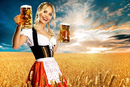 Happy and smiling sexy Bavarian oktoberfest girl waitress in traditional clothes, german dirndl, holding two big beer mugs in hands outdoor. Woman from Munich Germany Bavaria.