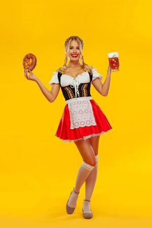 Junge Oktoberfest-Kellnerin, die ein traditionelles bayerisches oder deutsches Dirndl trägt und große Bierkrüge mit Getränk und Brezel serviert, einzeln auf gelbem Hintergrund. Foto in voller Höhe