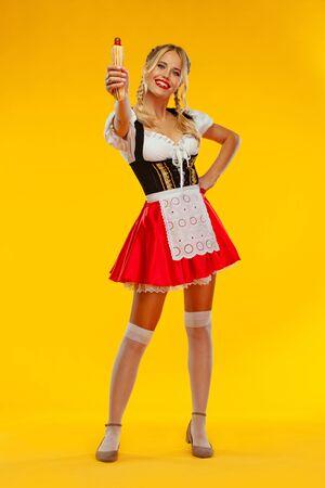 Junge Oktoberfest-Kellnerin, trägt ein traditionelles bayerisches oder deutsches Dirndl mit französischen Hot Dogs einzeln auf gelbem Hintergrund. Foto in voller Höhe.