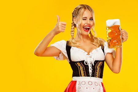 Wow Emotion, Frau mit Daumen hoch. Junge Oktoberfest-Kellnerin, die ein traditionelles bayerisches oder deutsches Dirndl trägt und großen Bierkrug mit Getränk auf gelbem Hintergrund serviert. Standard-Bild
